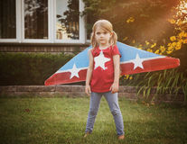 Little Pilot Child Pretending to Fly with Wings. A little child is wearing homemade cardboard flying wings with stars on them pretending to be a pilot for a Royalty Free Stock Image