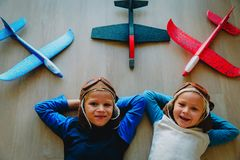 Little pilots- happy kids with helmet and glasses play with toy planes. Little pilots- happy boy and girl with helmet and glasses play with toy planes royalty free stock images
