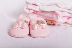 Little pink baby shoes and baby clothes Stock Photography