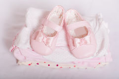 Little pink baby shoes and baby clothes Stock Photos
