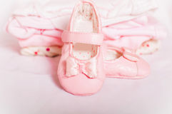 Little pink baby shoes and baby clothes Royalty Free Stock Photography