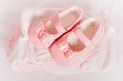 Little pink baby shoes and baby clothes Stock Image
