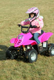 Little Pink Four Wheeler Quad Girl 1. A little girl riding a pink four wheeler quad in her backyard Royalty Free Stock Images