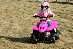 Little Pink Four Wheeler Quad Girl 2. A little girl riding a pink four wheeler quad in her backyard Royalty Free Stock Photography