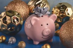 Little pink piggy bank with a bow on the head close-up. Nearby are a lot of gold and silver Christmas balls of various. Sizes. The symbol of the new year stock image