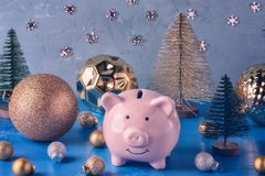 Little pink piggy bank in a magical forest of Christmas balls and decorative Christmas trees. Unusual holiday picture stock photo