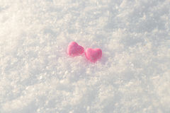 Little pink shiny hearts. In the snow Stock Photo