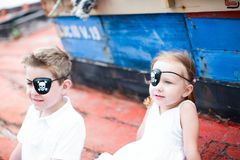 Little pirates. Cute little pirates boy and girl sitting at old boat Royalty Free Stock Photos