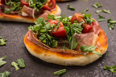 Little pizza with ham, tomato and rucola Royalty Free Stock Image