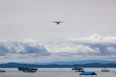 Little plane landing. With clouds and boats Royalty Free Stock Photo