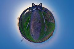 Little Planet Landscape After Sunset. Little planet (stereographic) projection of a disused former railway line with an iron bridge just after sunset on the Stock Photos