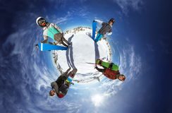 Little planet with snowboarders on blue sky backdrop. Little planet with bright color snowboarders posing on blue sky backdrop. Sheregesh, Siberia, Russia royalty free stock photo