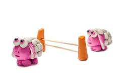 Little plasticine sheep jumping over a fence. Two little plasticine sheep jumping over a fence. White background stock photo