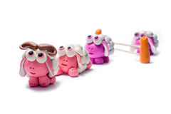 Little plasticine sheep jumping over a fence. White background stock image