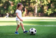 Little player: toddler boy in sports uniform playing footbal at soccer field in summer day outdoors. Child ready to kick ball royalty free stock image