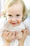 Little playful girl. Little playful blue-eyed girl in mother hands Royalty Free Stock Photo