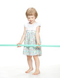 Little playful girl in dress holding sport stick Royalty Free Stock Photo