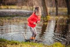 Charming girl playing in puddle Royalty Free Stock Image
