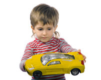 Little playing boy. Little boy plays with his yellow toy car Stock Photo