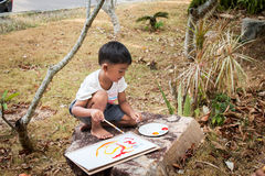 Little playing panit on white paper. In the park Stock Images