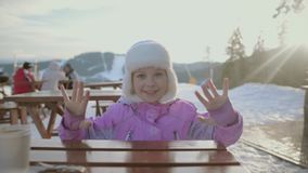 Little plays at the dinner table in the midst of snow-capped mountains. Around leisure and entertainment, people have lunch and go skiing and snowboarding stock footage