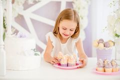 Little girl holding a pink plate with sweet cakes in the candy bar royalty free stock images