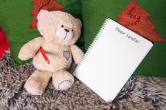 Little plush bear toy with pencil and blank notebook on a sofa. Stock Photos