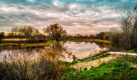 Little pond. A small pond and dramatic clouds during sunset Stock Photography