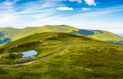 Little pond on top of mountain ridge. Gorgeous summer landscape with footpath through grassy hill and high clouds on a blue sky. wonderful tourism concept Royalty Free Stock Photo
