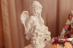 Little porcelain angel stands behind the bouquet Royalty Free Stock Images