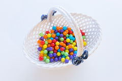 Little porcelain basket filled with  colorful candies on white b. Little porcelain basket filled with  colorful candies Royalty Free Stock Photography