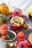 Little pot with pumpkin soup Stock Images