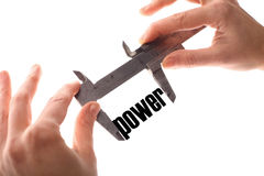 Little power. Color horizontal shot of two hands holding a caliper measuring the word power royalty free stock image