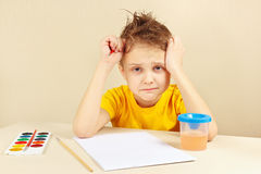 Little preoccupied artist in yellow shirt is thinking what to draw Royalty Free Stock Photo