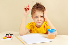 Little preoccupied artist in yellow shirt is thinking what to paint Royalty Free Stock Photography