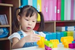 Little preschool age girl playing plastic blocks Royalty Free Stock Image