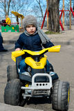 Little preschool boy driving big toy car, playing and having fun, outdoors. Royalty Free Stock Photo