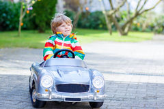 Little preschool boy driving big toy old vintage car, outdoors Stock Image