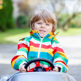 Little preschool boy driving big toy old vintage car, outdoors Royalty Free Stock Photos