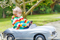 Little preschool boy driving big toy old vintage car, outdoors Royalty Free Stock Photography