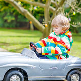 Little preschool boy driving big toy old vintage car, outdoors Stock Images