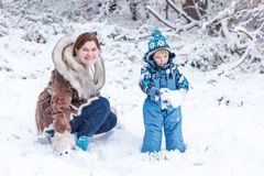 Little preschool boy and his mother playing with first snow in p Royalty Free Stock Photography