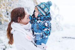 Little preschool boy and his mother playing with first snow in p Stock Photo