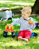 Little preschool boy playing with big toy car at city garden Stock Images