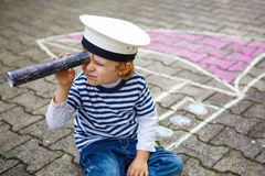Little preschool child having fun with ship picture drawing with Stock Images