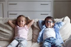 Little preschool girl and boy relaxing sitting on couch. Silent preschool sister and brother sitting on sofa in living room at home. Siblings closing eyes have stock photos