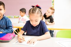Cute preschooler working in a classroom royalty free stock images