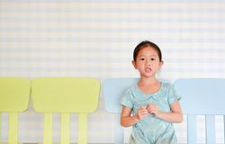 Little preschool girl in a Kindergarten room sitting on plastic baby chair looking at camera.  royalty free stock photo