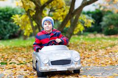Little preschool kid boy driving big toy old vintage toy car. And having fun, outdoors on beautiful autumn day. Active leisure with children in fall park with Stock Photos