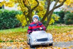 Little preschool kid boy driving big toy old vintage toy car Stock Image